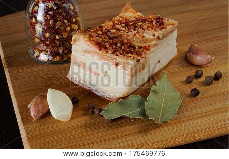 Lard with garlic and spices on the board