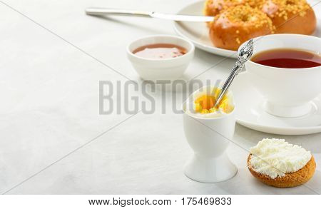 Delicious and healthy breakfast of boiled egg and brioche buns with black tea on a light background. Copy space soft focus.