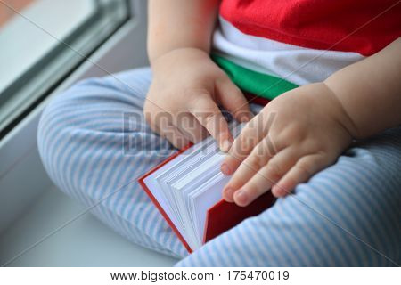 Baby boy reading a book, dclose up of hands Leafing through the pages.