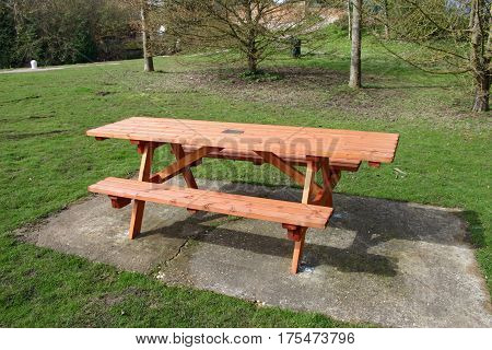 Wooden picnic table on concrete base in a grassed picnic site with a background of trees.