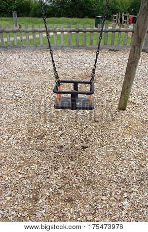 Park swing for a young child where the chipped bark is wearing away underneath. Fence litter bin grass and trees in the background.