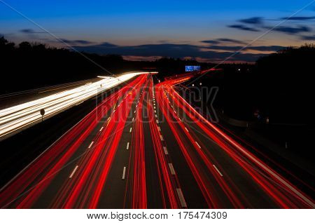 Light trails of vehicles in a motorway at sunset