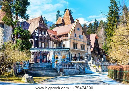 Colorful authentic romanian house in countryside, Romania near Peles castle, snow mountains behind