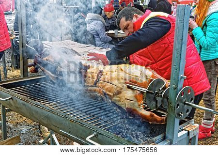 KHMELNYTSKY UKRAINE - FEBRUARY 25 2017: Mature man treats a pig on a metal skewer outdoor municipal public holiday before Orthodox Pancake Day in Khmelnytsky Ukraine