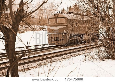 Single diesel locomotive moves across the railway tracks in wintertime sepia