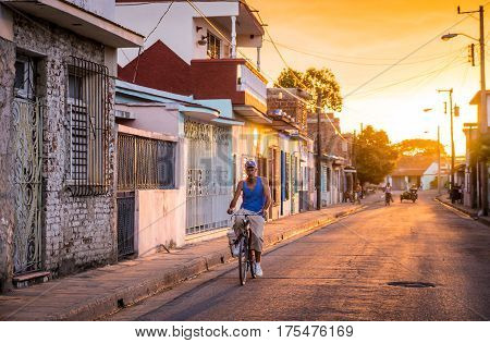 Camaguey, Cuba on January 2, 2016: Cuban man riding his bicycle through a street in the historic Caribbean city center of Camaguey at sunset