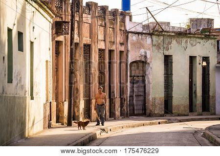 Man with dog walking in a street in Camaguey's historic old town
