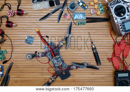 Assembly drone accessories quadcopter on a wooden background, space for ads and inscriptions