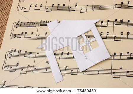 Paper house placed on a paper with musical notes