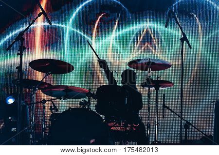 Rock band performs on stage. Musician drummer silhouette in the concert. silhouette of drum player in action on stage in front of concert crowd.