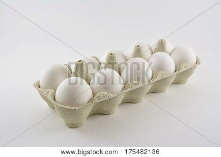 Dozen white chicken eggs in a box.