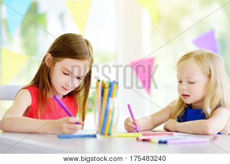 Two Cute Little Sisters Drawing With Colorful Pencils At A Daycare. Creative Kids Painting Together.