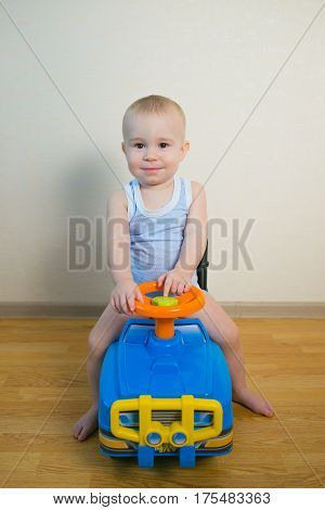 Cute Baby boy driving a toy car at home.