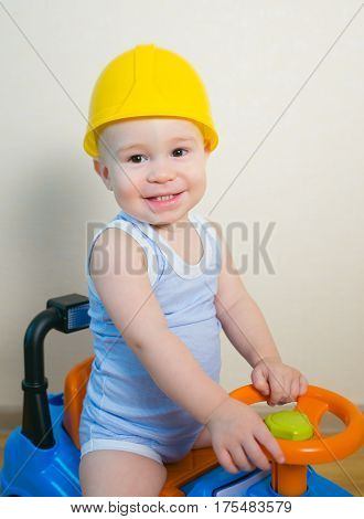 Happy smiling kid in yellow helmet driving a toy car.
