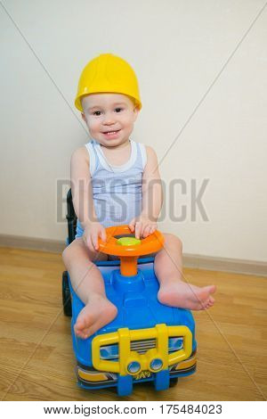 Happy smiling Baby boy driving a toy car at home.
