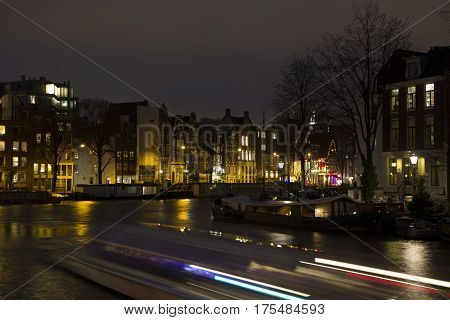 Night time Amsterdam with ferry light trail