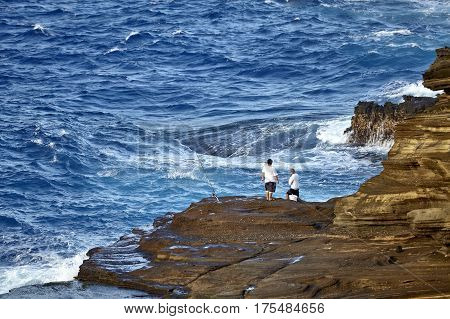 Makapuu Point, Hawaii, USA -- Unidentified island fisherman brave the rough surf off Makapuu Point on the island of Oahu, Hawaii.