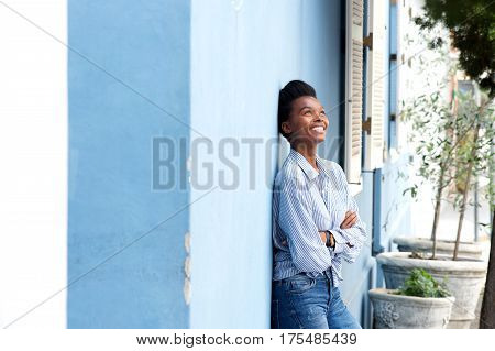 Happy Young Black Woman Leaning Against Wall