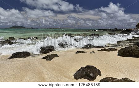 Tropical island sandy beach shoreline surf and rocky shore