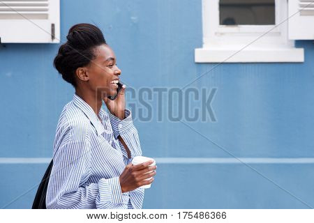 Young Black Woman Walking And Talking On Cellphone