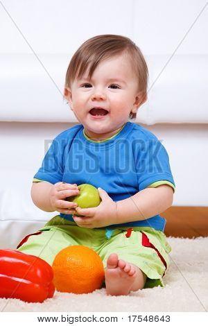 Laughing baby boy sitting with ripe fruit