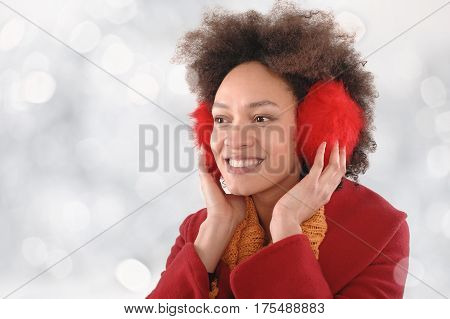 Happy Young Woman With Earmuffs Posing In The Studio