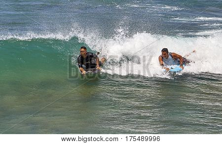 Waikiki Beach, Hawaii, USA -- August 2, 2016: Boogie board surfers catch a wave off Waikiki Beach Hawaii USA