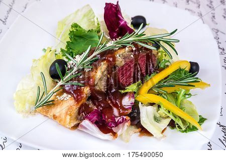 Veal with mushrooms in puff pastry and vegetables on a white plate