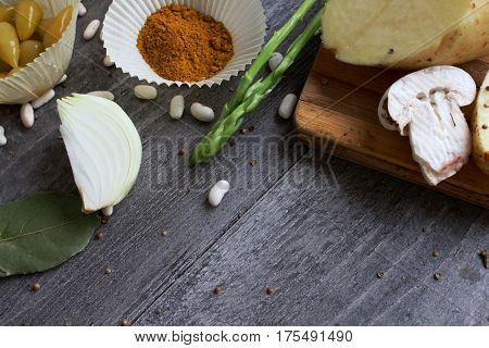 Grey Wooden Table With Vegetables, Onions, Mushrooms, Peppers, Asparagus And Spices. Process Of Cook