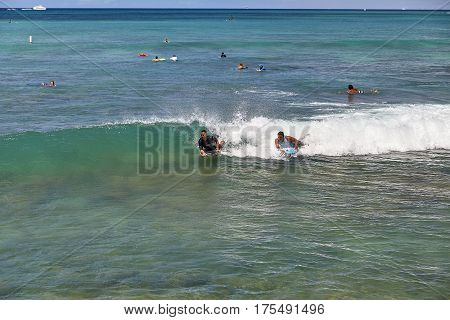 Waikiki Beach, Hawaii, USA -- August 2, 2016: Boogie board surfers catch a wave off the shores of Waikiki in Hawaii