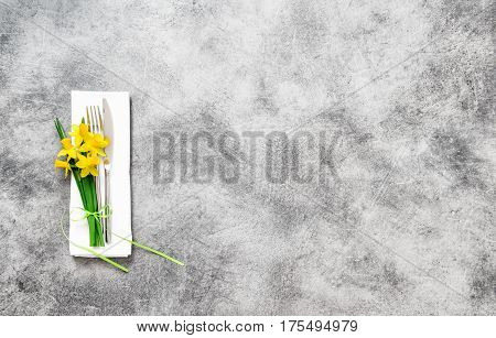 Fork knife and napkin with spring flowers decoration. Festive table place setting