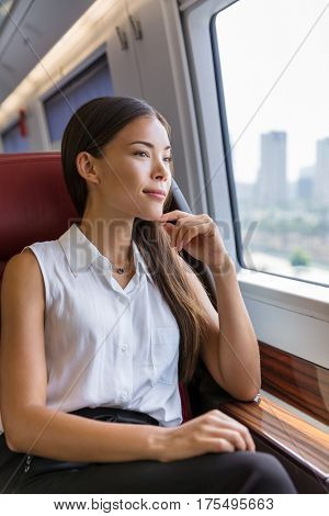 Woman enjoying view in train commute. Woman relaxing enjoying view during morning commute. Business class seat in train. Asian businesswoman pensive looking out the window in travel transport.
