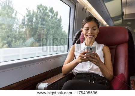 Smiling Asian businesswoman using smartphone social media app while commuting to work in train. Woman sitting in transport enjoying travel.