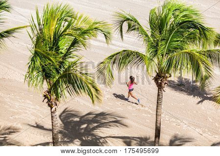 Fitness woman running training on tropical beach in between palm trees. View from high angle, hero shot. Health and sports concept. Copyspace.