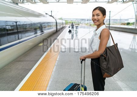 Asian traveler waiting for travel on train platform. Business woman standing with luggage at central railway station ready to leave for holiday trip.