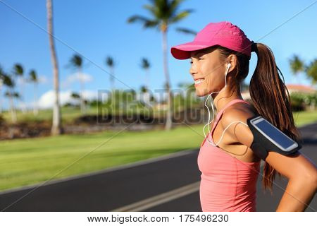 Happy fitness girl runner listening to running motivation music on smartphone app with earphones. Asian woman athlete wearing cap and armband phone holder outdoor on city road.