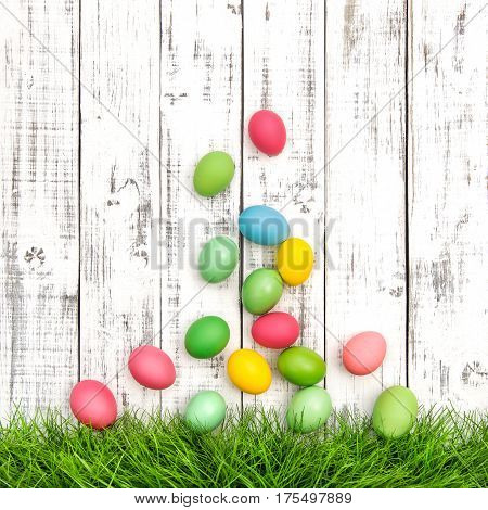 Easter eggs in green grass on bright wooden background. Colorful Easter decoration