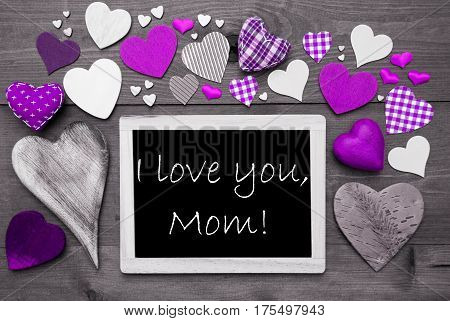 Chalkboard With English Text I Love You Mom. Many Purple Textile Hearts. Grey Wooden Background With Vintage, Rustic Or Retro Style. Black And White Style With Colored Hot Spots