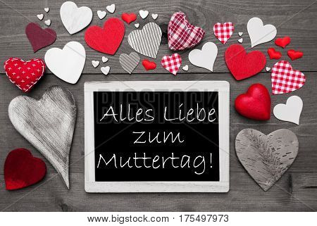 Chalkboard With German Text Alles Liebe Zum Muttertag Means Happy Mothers Day. Red Textile Hearts. Grey Wooden Background With Vintage, Or Retro Style. Black And White Style With Colored Hot Spots