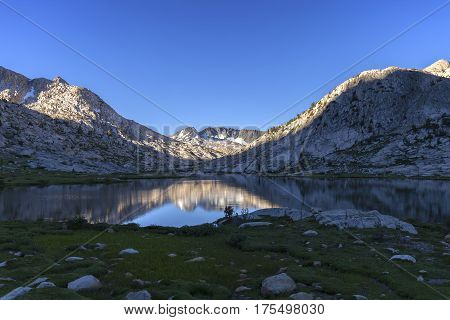 Evolution Light - First morning sunlight pours across Evolution Lake in the Sierra Nevada on the Pacific Crest Trail.