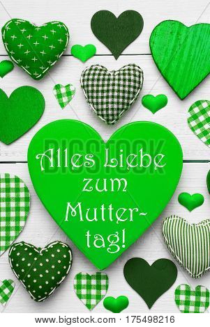 Green Vertical Heart Texture With German Text Alles Liebe Zum Muttertag Means Happy Mothers Day. White Wooden Background. Textile Hearts Which Are Dotted and Striped. Greeting Card For Congratulations