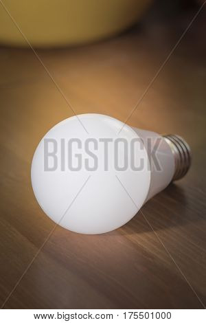 Burning light bulb with frosted glass lying on a brown desk without a network connection
