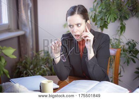 Young woman receiving shocking news while on work