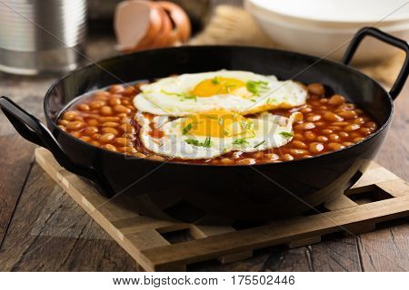 Baked beans with fried eggs and chives served in a pan.