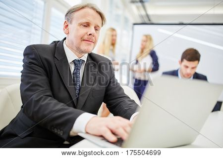 Man consultant with laptop in business meeting in conference room