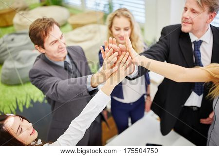 Business people give each other a high five in the office for the successful teamwork