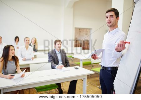 Young man as a lecturer in a seminar with a flipchart explaining a business strategy