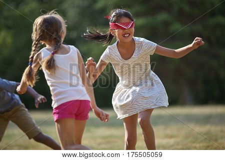 Happy children playing blind man's buff in summer at a birthday party