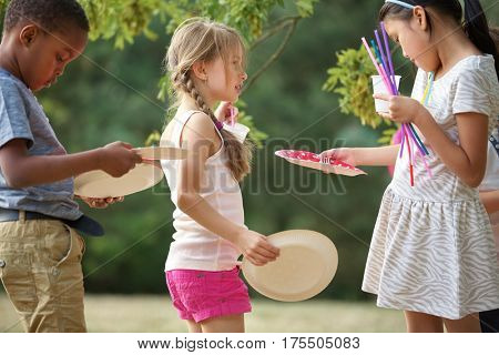 Interracial group of kids distribute plates at a birthday party