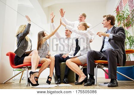 Successful busines team congratulates each other with a group high five and motivates each other in the office